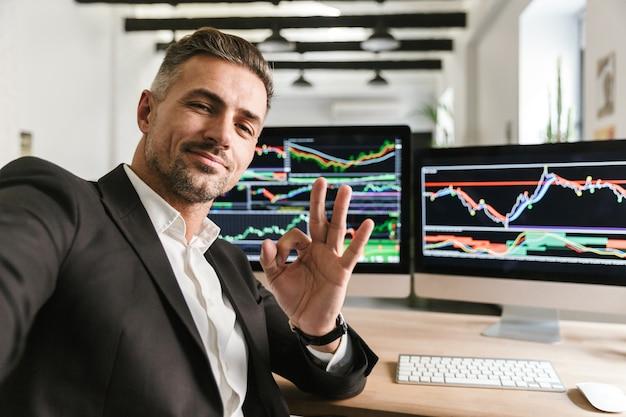 Foto des kaukasischen mannes 30s, der anzug trägt, der selfie nimmt, während im büro am computer mit grafiken und diagrammen am bildschirm arbeitet