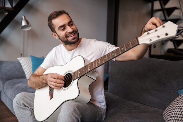Foto des kaukasischen mannes 30s, der lässiges t-shirt trägt, das akustische gitarre spielt, während auf sofa in wohnung sitzt