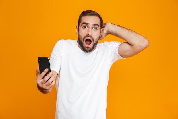 Foto des kaukasischen mannes 30s in der freizeitkleidung, die smartphone hält, lokalisiert