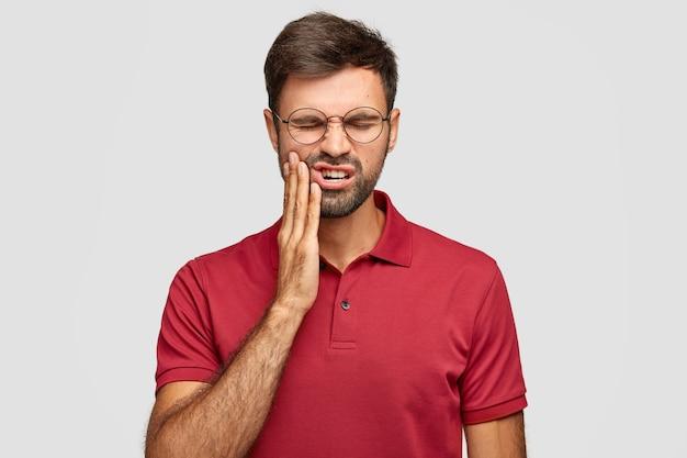 Foto des kaukasischen mannes leidet unter schmerzhaften zahnschmerzen, hat verfaulten zahn, muss zahnarzt besuchen