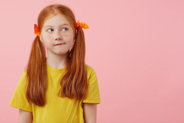 Foto des kleinen denkens sommersprossen rothaariges mädchen mit zwei schwänzen, schaut weg, berührt wangen, trägt im gelben t-shirt, steht über rosa hintergrund mit kopienraum.
