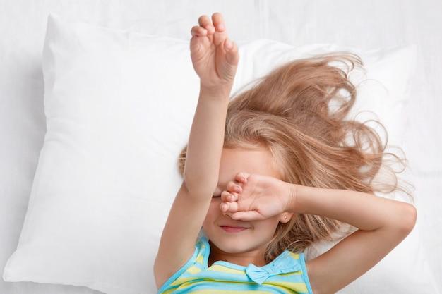 Foto des kleinen entzückenden niedlichen kindes bedeckt augen