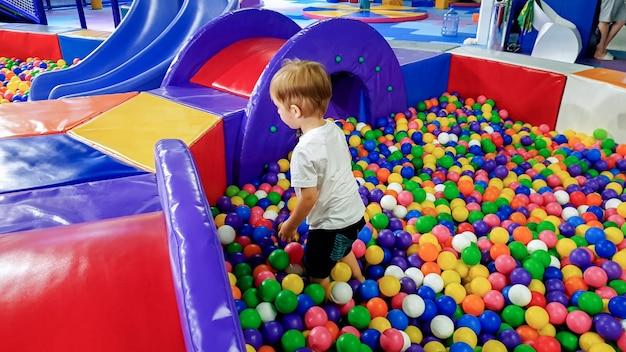 Foto des kleinen jungen, der im pool voller bunter plastikbälle spielt. kleinkind hat spaß auf dem spielplatz im einkaufszentrum?