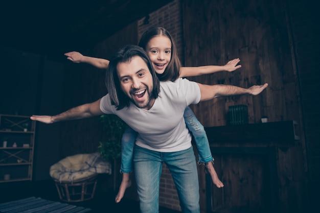 Foto des kleinen lustigen energetischen mädchens aufgeregt hübscher papa tragen tochter, die spiele gute laune spielt, die freizeit verbringt