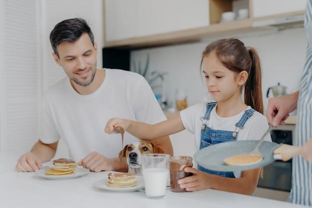 Foto des kleinen mädchens in den denimlatzhosen fügt schokolade pfannkuchen hinzu, frühstückt zusammen mit vati und hund, mag, wie mutter kocht. familie in der küche frühstücken am wochenende. glücklicher moment