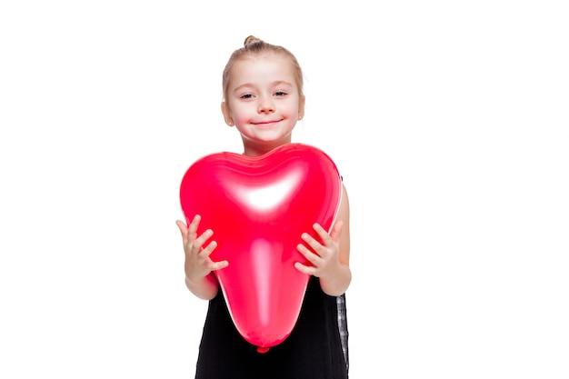 Foto des kleinen mädchens in einem schwarzen eleganten kleid, das einen roten ballon in der form eines herzens hält