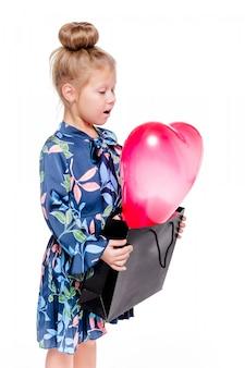 Foto des kleinen modischen mädchens in einem blauen blumenkleid hält eine große tasche mit einem herzförmigen ballon innen