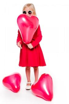 Foto des kleinen modischen mädchens in einem roten kleid, das einen roten herzförmigen ballon hält
