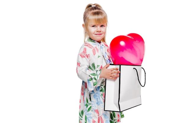 Foto des kleinen modischen mädchens in einem weißen blumenkleid hält eine große tasche mit einem herzförmigen ballon innen.