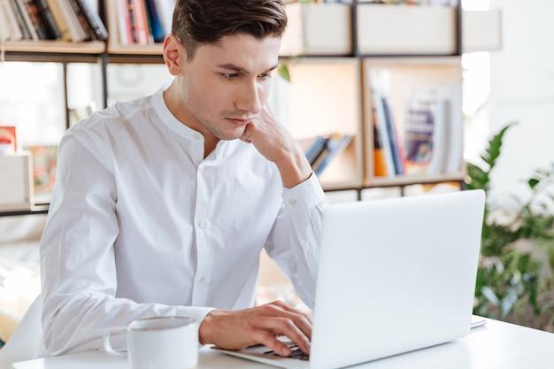 Foto des konzentrierten mannes im weißen hemd mit laptop-computer gekleidet. coworking. schauen sie sich den laptop an.