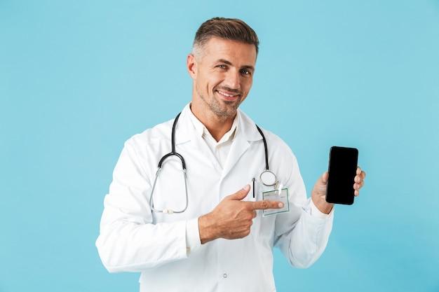 Foto des lächelnden arztes, der weißen kittel und stethoskop hält handy hält, lokalisiert über blauer wand