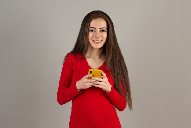 Foto des lächelnden entzückenden mädchens im roten sweatshirt, das mobiltelefon auf grauer wand hält.