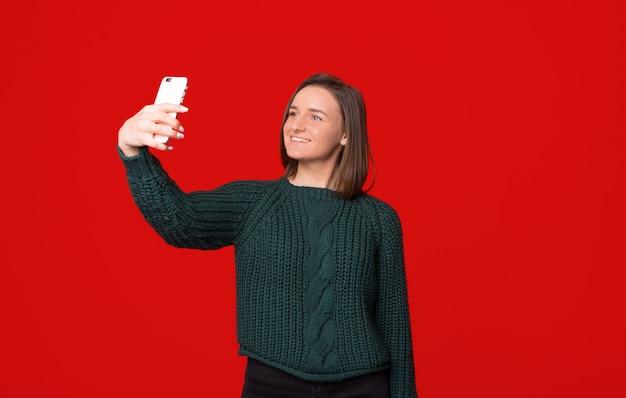 Foto des lächelnden jungen mädchens, das selfie foto auf smartphone über rotem lokalisiertem hintergrund nimmt