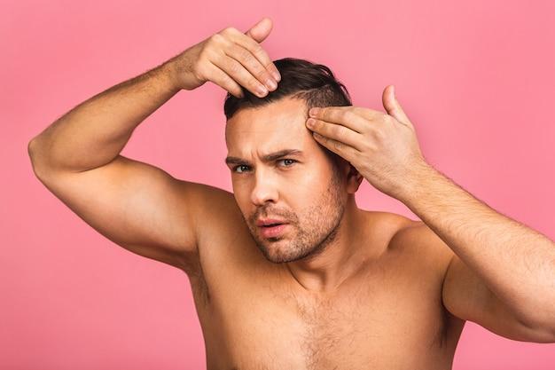 Foto des lächelnden jungen schönen mannes, der nackt steht. mann-hautpflegekonzept in einem badezimmer.