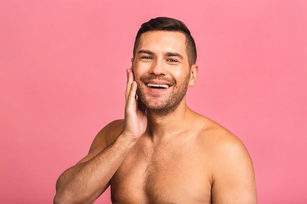 Foto des lächelnden jungen schönen mannes, der nackt steht. mans hautpflegekonzept in einem badezimmer.