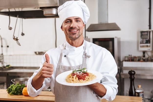 Foto des lächelnden männlichen chefs in der weißen uniform, die platte mit mahlzeit hält