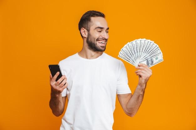 Foto des lächelnden mannes 30s in der freizeitkleidung, die handy und fan des geldes hält, lokalisiert