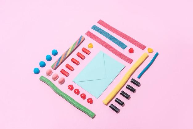 Foto des leeren papierumschlags mit bunten süßen zuckersüßigkeiten
