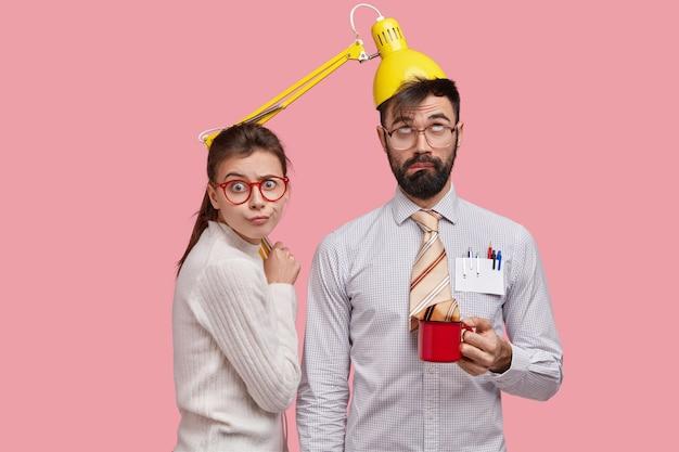 Foto des lustigen bärtigen jungen mannes hat lampe auf kopf, krawatte in der tasse tee, gekleidet in formelle kleidung, seine partnerin steht in der nähe