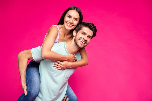 Foto des lustigen kerls und der dame, die huckepack halten, die beste freizeit verbringen, tragen freizeitkleidung, die lebhaften lebendigen rosa farbhintergrund lokalisiert