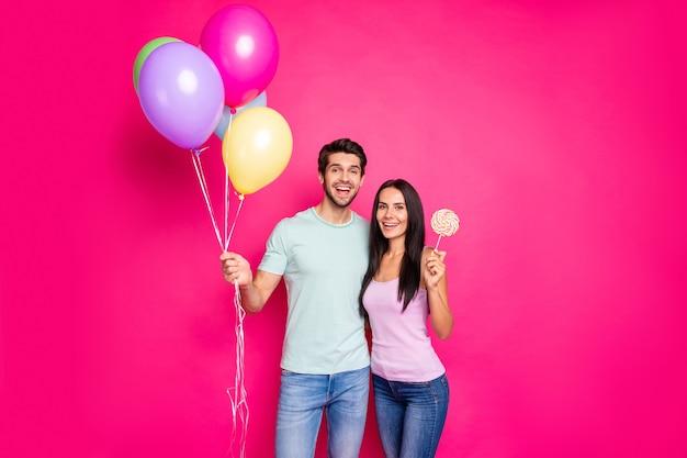Foto des lustigen kerls und der dame, die luftballons in den händen halten, kam zur geburtstagsfeier der eltern mit zuckerbonbon tragen lässiges outfit lokalisierten rosa farbhintergrund