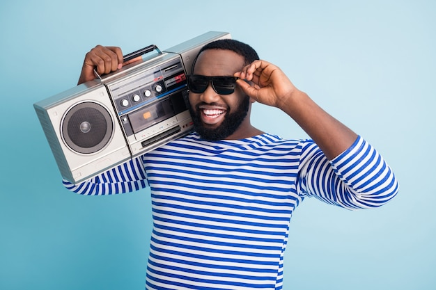 Foto des lustigen kühlen selbstbewussten kerls halten retro-kassettenrekorder