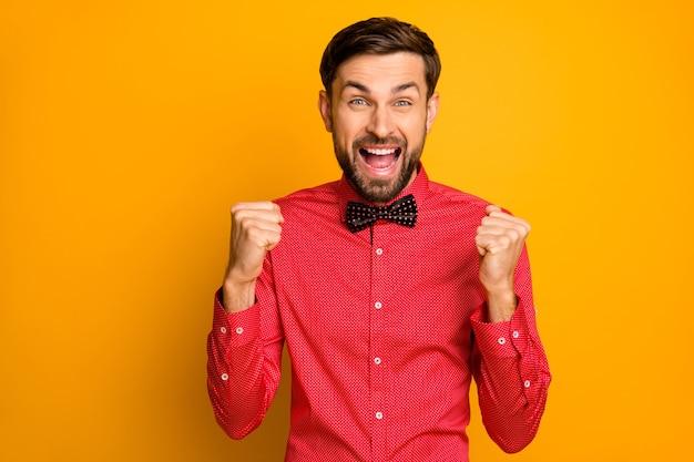 Foto des lustigen macho-kerls gute laune offener mund, der lotteriegeld gewinnt, erhöht die erhobenen fäuste aufgeregt trägt stilvolles rotes hemd mit schwarzer fliege