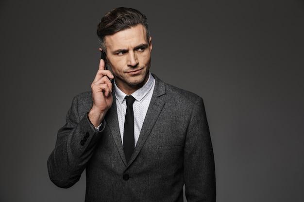 Foto des männlichen mannes 30s gekleidet in sachlichem kostüm, das im büro arbeitet und am telefon über geschäft spricht, lokalisiert über graue wand