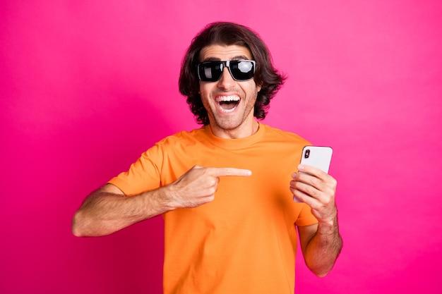 Foto des mannes hand direkter zeigefinger halten telefon tragen orangefarbenes t-shirt sonnenbrille isoliert rosa hintergrund