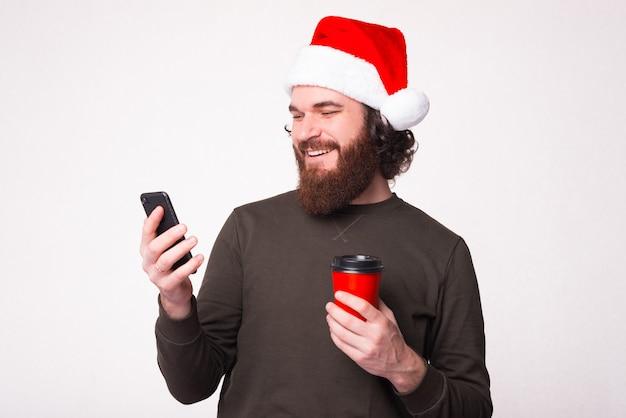 Foto des mannes mit bart, der weihnachtshut trägt und smartphone über weißer wand verwendet