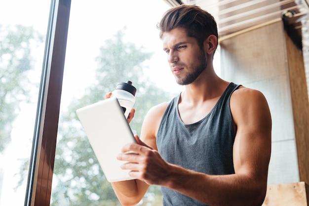 Foto des modells im fitnessstudio mit tablet und flasche