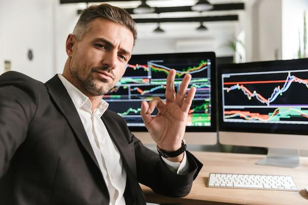 Foto des modernen mannes 30s, der anzug trägt, der selfie nimmt, während im büro am computer mit grafiken und diagrammen am bildschirm arbeitet