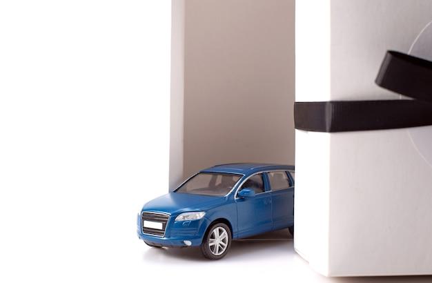 Foto des modischen autos des spielzeug-blauen geländewagens, das aus der weißen geschenkbox mit großem schwarzen bogen lokalisiert über weißem hintergrund fährt.