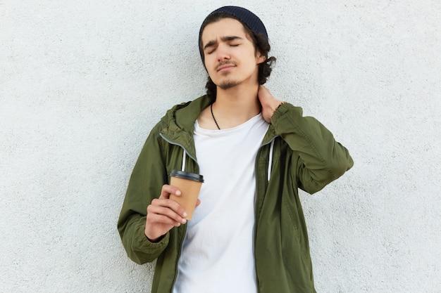 Foto des müden lockigen mannes hält hand am hals, gekleidet in modische kleidung, hält aromatischen kaffee oder cappucino