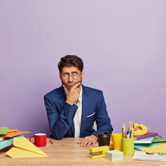 Foto des nachdenklichen geschäftsmannes, der am schreibtisch sitzt