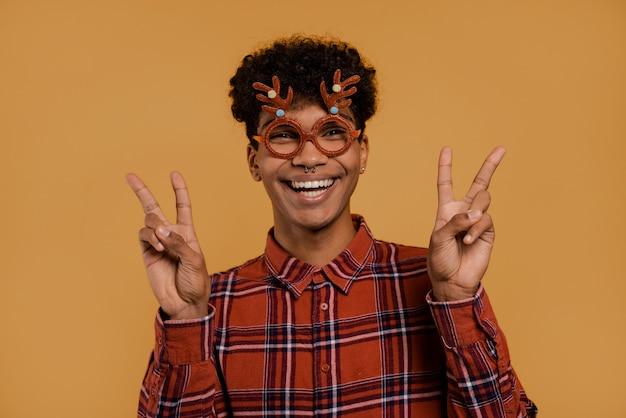 Foto des niedlichen afrikanischen männlichen bauern trägt weihnachtsbrille und lächelt, zeigt frieden und liebe. mann trägt kariertes hemd, isolierten braunen farbhintergrund.