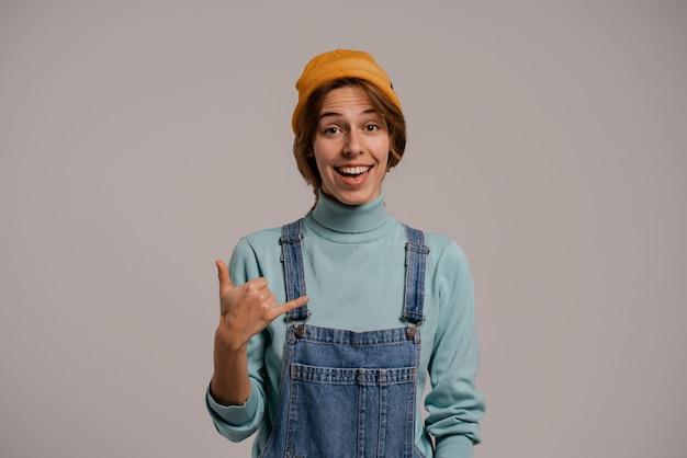 Foto des niedlichen weiblichen hipsters zeigt geste, die mich anruft. weiße frau trägt jeans insgesamt und hut isolierten grauen farbhintergrund.
