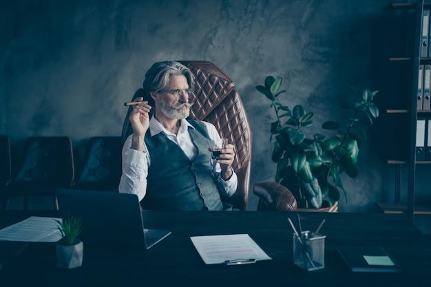 Foto des noblen ernsten geschäftsmannes, der im büro alkohol raucht, der zigarre raucht