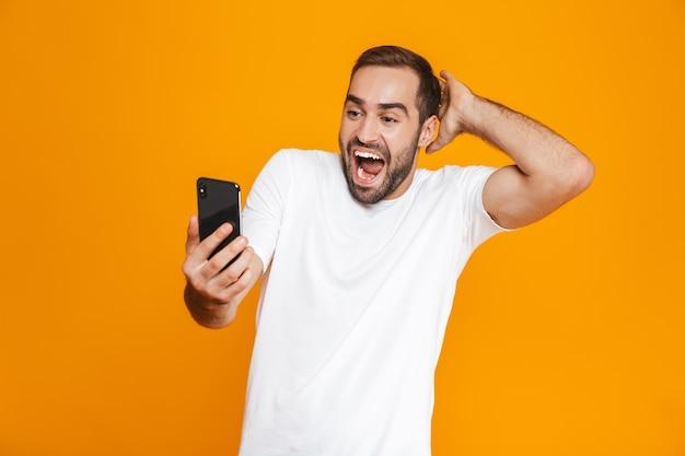 Foto des optimistischen mannes 30s in der freizeitkleidung lächelnd und hält smartphone, lokalisiert