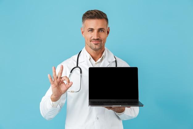 Foto des optimistischen mannes, der weißen medizinischen mantel und stethoskop hält laptop hält, lokalisiert über blauer wand