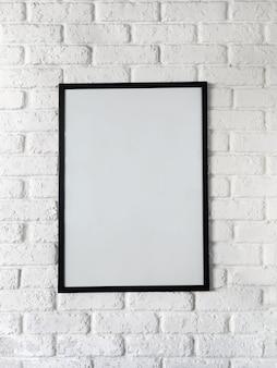 Foto des plakats in einem schwarzen rahmen auf einer weißen backsteinmauer.
