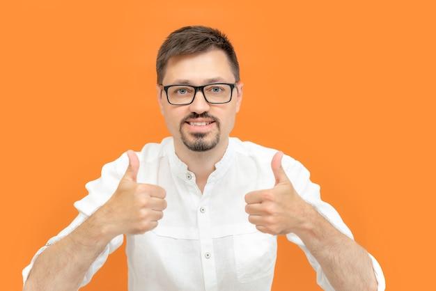 Foto des positiven glücklichen mannes zeigt daumen hoch zeichen mit zwei händen lokalisiert über orange farbhintergrund. männliches studioportrait.
