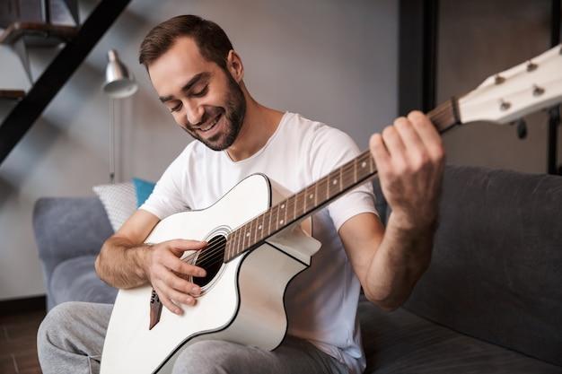 Foto des positiven mannes 30s, der lässiges t-shirt trägt, das akustische gitarre spielt, während auf sofa in wohnung sitzt