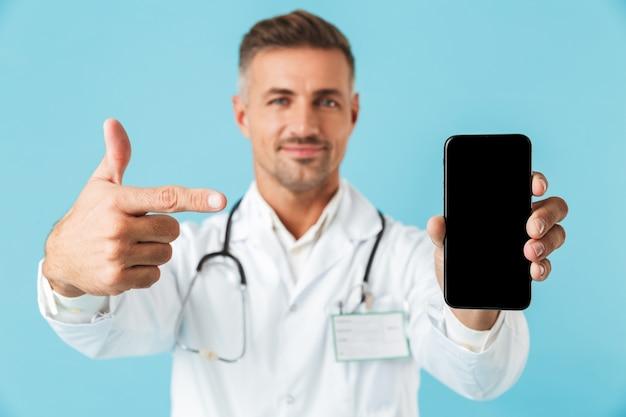 Foto des professionellen arztes, der weißen kittel und stethoskop hält handy trägt, lokalisiert über blauer wand