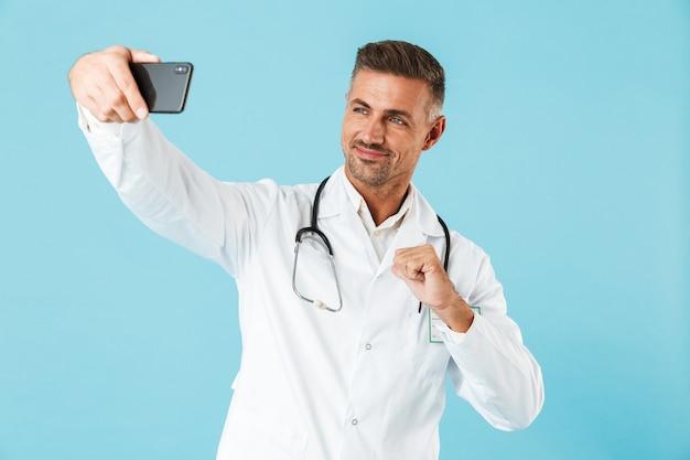 Foto des reifen arztes, der weißen kittel und stethoskop trägt, das selfie auf handy nimmt, lokalisiert über blauer wand