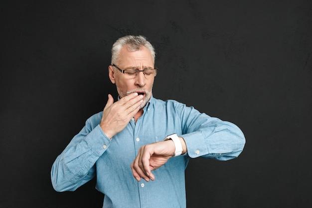 Foto des reifen unrasierten mannes 60s mit grauem haar, das brillen trägt, die seine armbanduhr mit verwirrung betrachten, lokalisiert über schwarzer wand