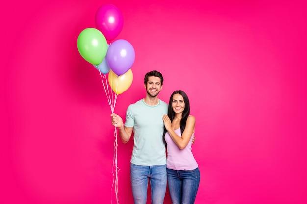 Foto des reizenden kerls und des damepaares, das luftballons in den händen hält, kam zu den elterngeburtstagsfeier tragen lässiges outfit lokalisiert rosa farbhintergrund