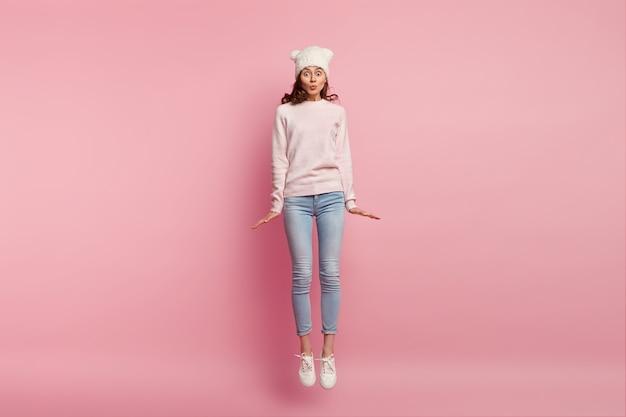 Foto des reizenden mädchens springt in luft gegen rosa raum, trägt hut, pullover, jeans und turnschuhe, hält lippen gefaltet