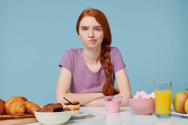 Foto des rothaarigen mädchens, das kamera mit unzufriedenheit des zorns schaut, zweifel denkt über diät, zusätzliche kalorien, backnahrung und frisches obst nach