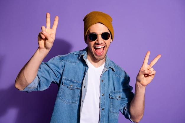 Foto des schönen attraktiven jungen hipster-mannes, der sie doppeltes v-zeichen mit aufgeregtem gesichtsausdruck zeigt, lokalisiert über lila lebendigem farbhintergrund